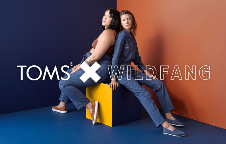 Two models sitting and wearing TOMS x Wildfang shoes.