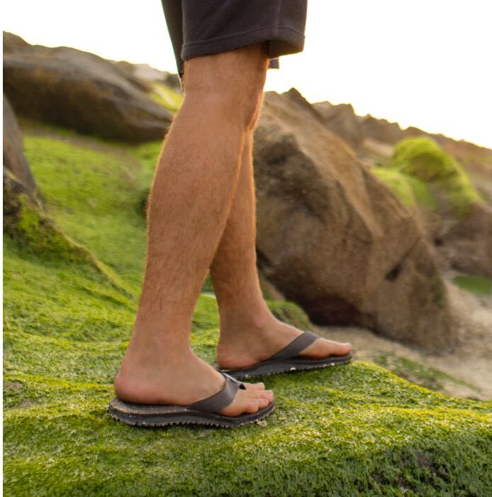 Man wearing TOMS X Outerknown sandals standing on grassy hill
