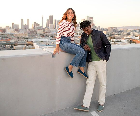 A young man and woman wearing classic TOMS alpargatas hanging out together with the Downtown Los Angeles skyline in the distance.