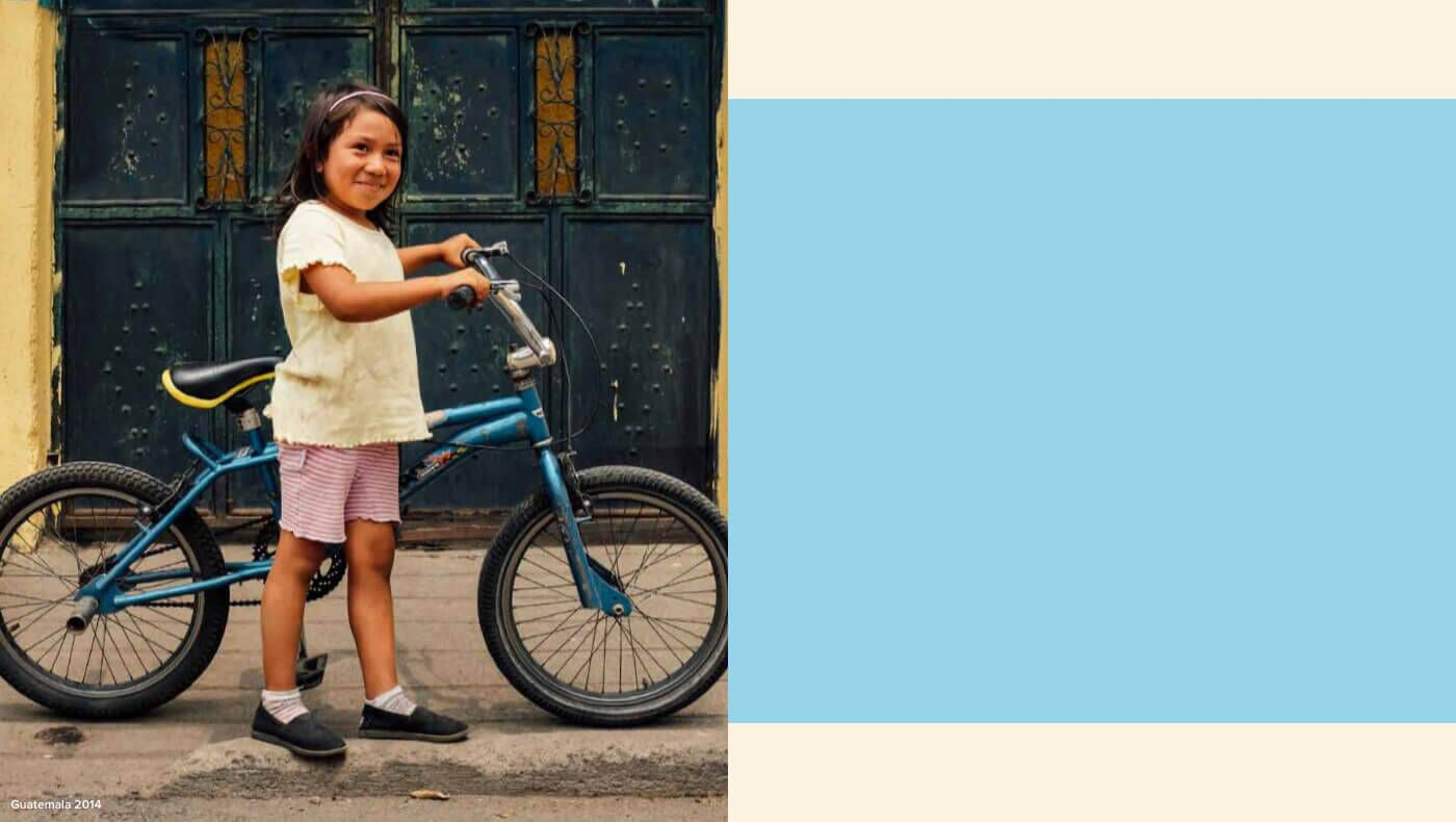 A girl from Guatemala standing next to her bike wearing TOMS Giving shoes.