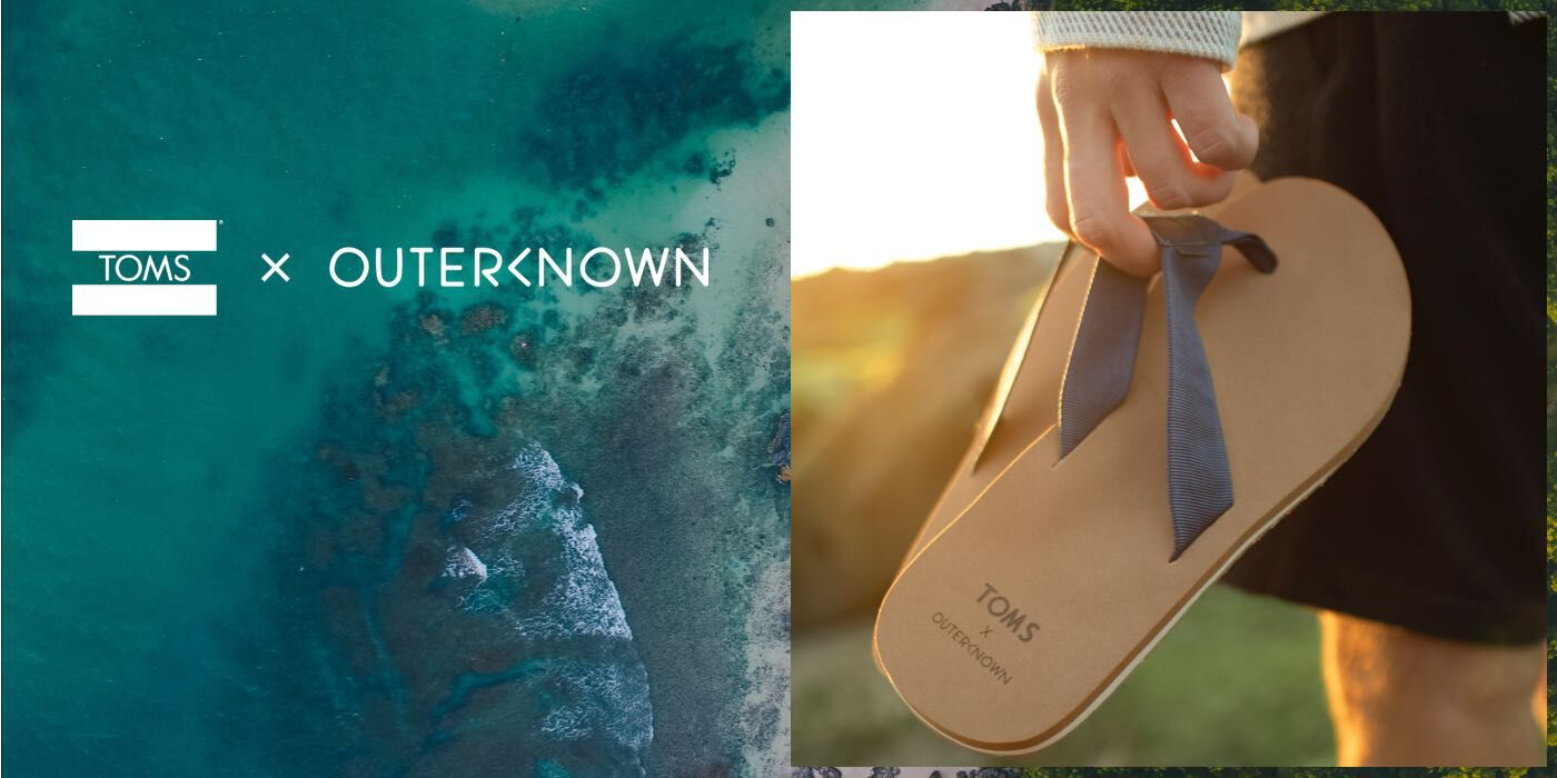 Green ocean and someone holding a pair of TOMS X Outerknown sandals