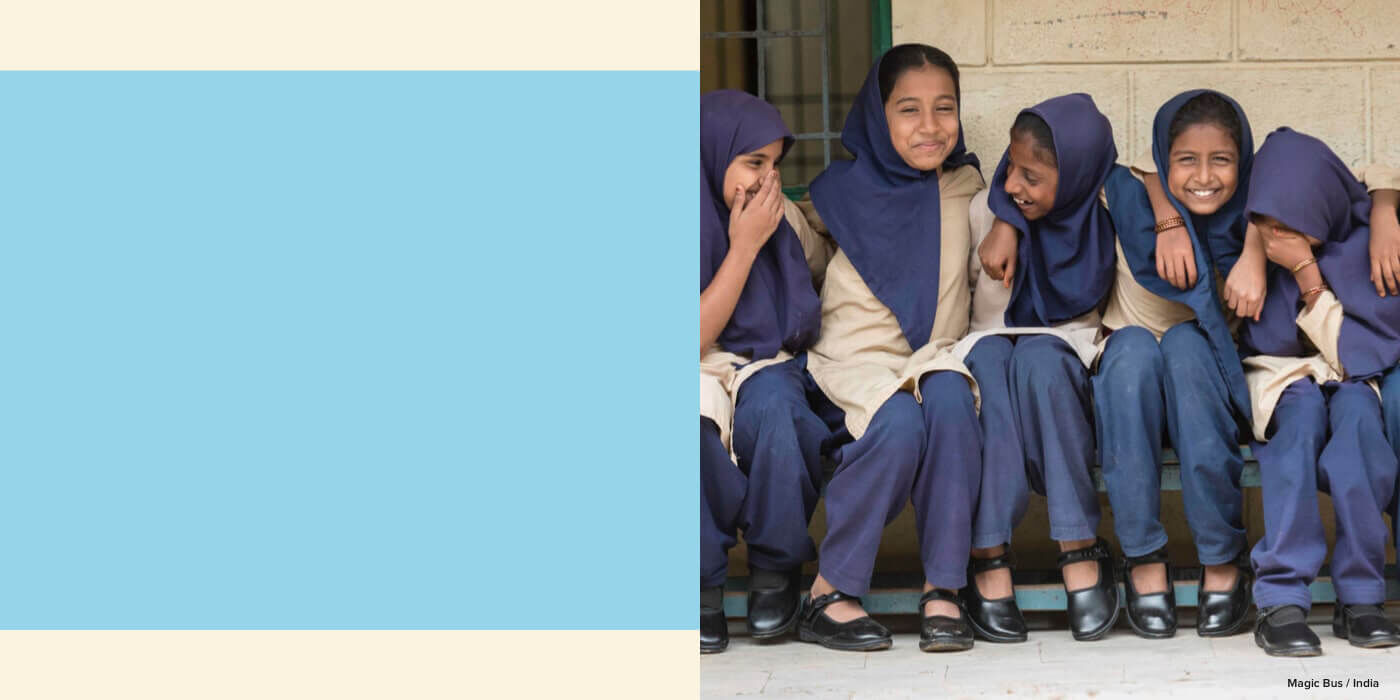 School girls sitting on a bench smiling. Text on bottom right corner: Magic Bus / India.