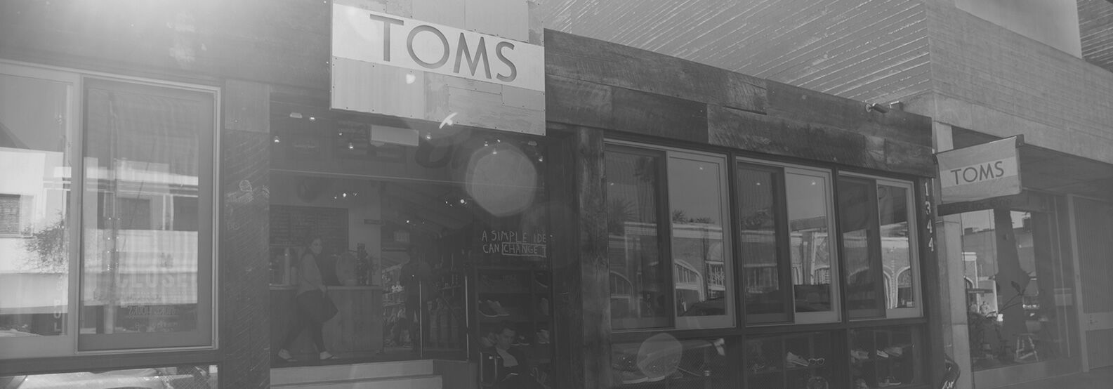 A black and white image of a TOMS storefront