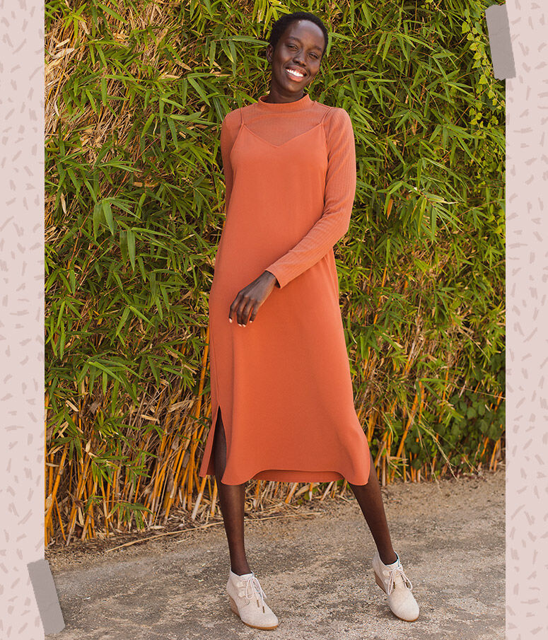 Women's Kala Boots on a model in a bright orange dress over a turtle neck long sleeve t-shirt standing in front of a bamboo backdrop
