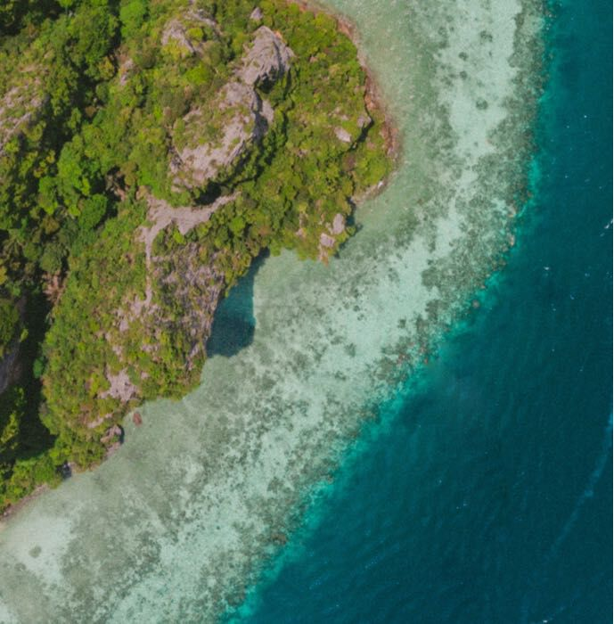 Arial view of ocean coastline with turquoise water and  green rocky shore