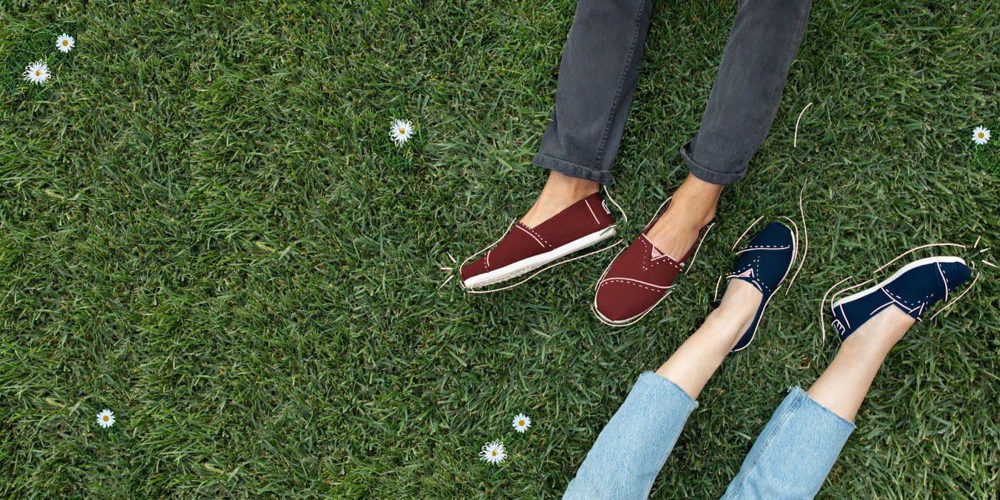 Two people on the grass wearing the Black Cherry Heritage Canvas CloudBound Men's Alpargatas and Majolica Blue Heritage Canvas CloudBound Women's Alpargatas.