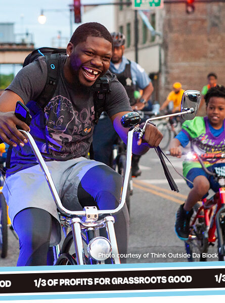 A group of people smiling while riding their bikes. Caption: photo courtesy of Think Outside Da Block. 1/3 of profits for Grassroots Good.