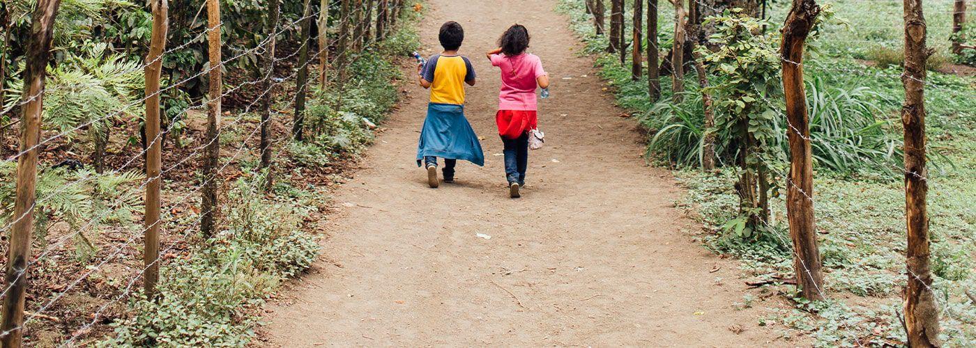 Two children walking away down a dirt path