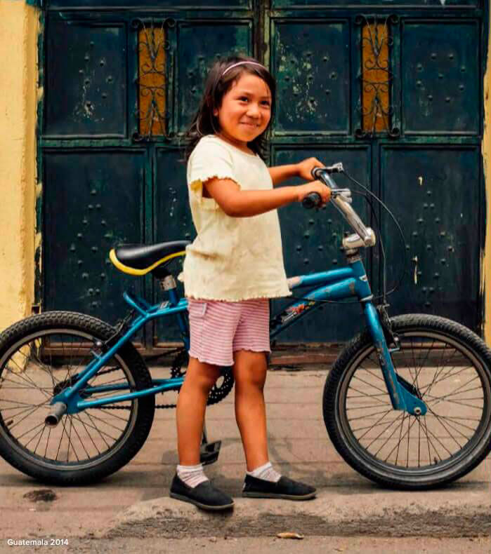 Image: A girl from Guatemala standing next to her bike wearing TOMS Giving shoes.
