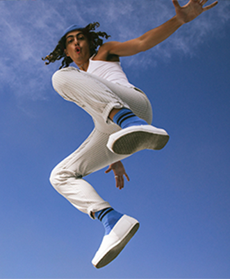 Model jumping in the air wearing white Alpargatas.