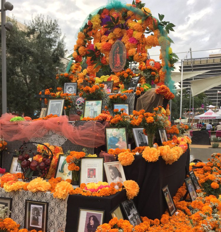 A man looking at images of the dead at a Dia De Los Muertos event.