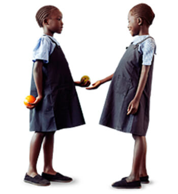 Two young school girls in uniform exchanging food