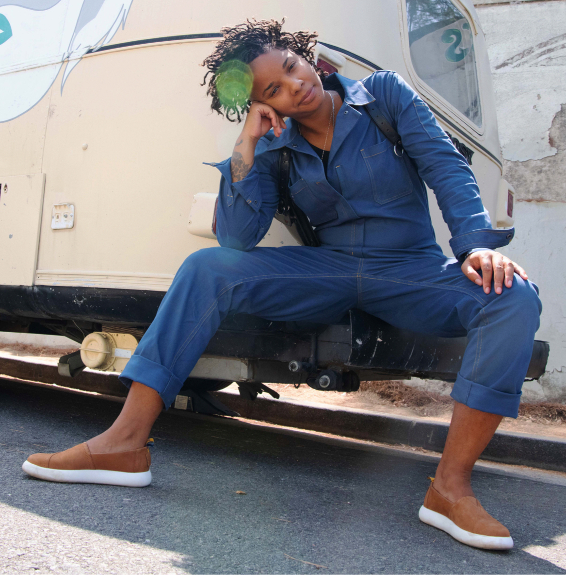Model wearing the TOMS x WILDFANG Coverall in Dark Denim and Alpargata Mallow™ slip on in premier tan leather is shown.