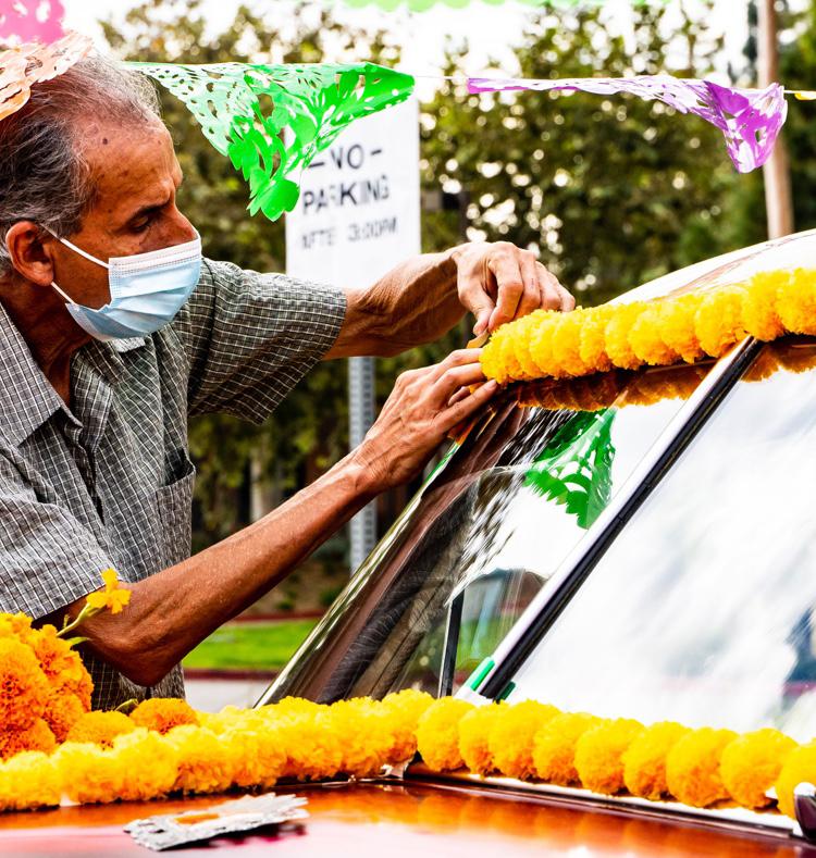A man decorating his car with carnations at a a Dia De Los Muertos event.