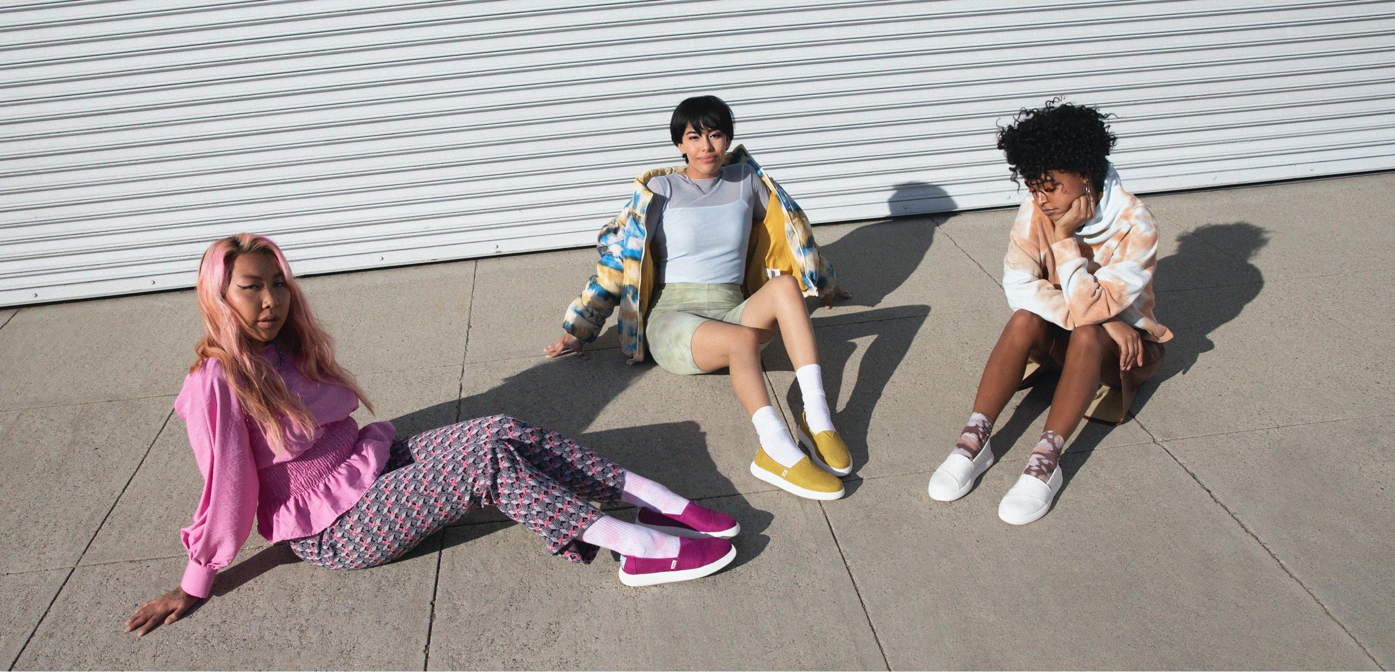 Models sitting together wearing Alpargata Mallow in fuchsia, dark mustard, and white styles.