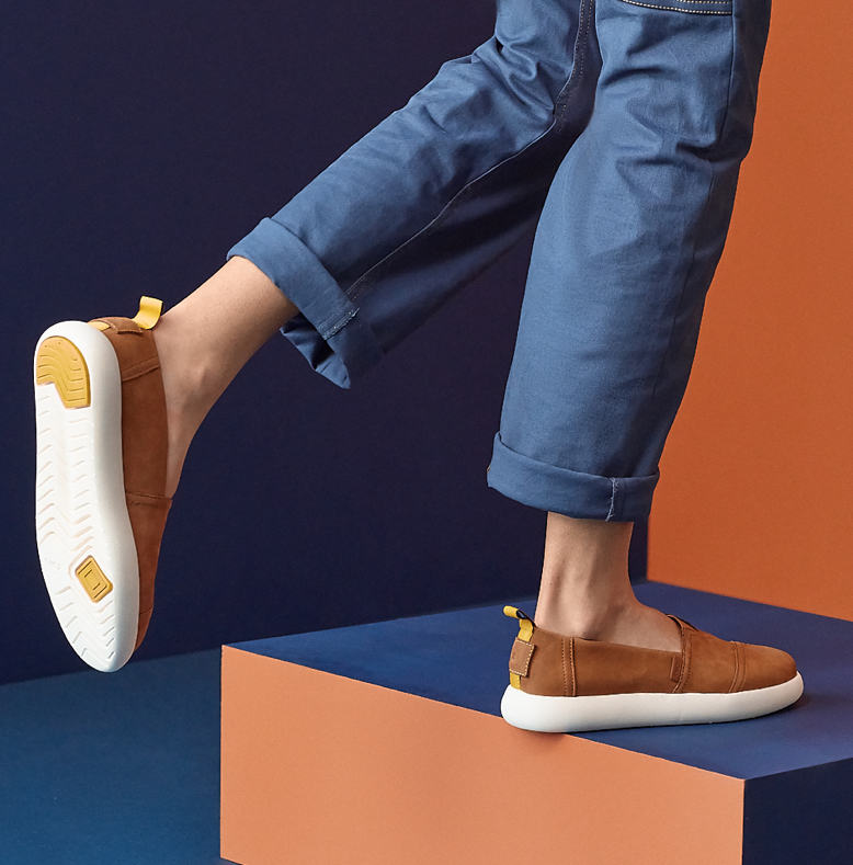 Feet view of model wearing TOMS x WILDFANG Alpargata Mallow™ slip on in premier tan leather is shown.